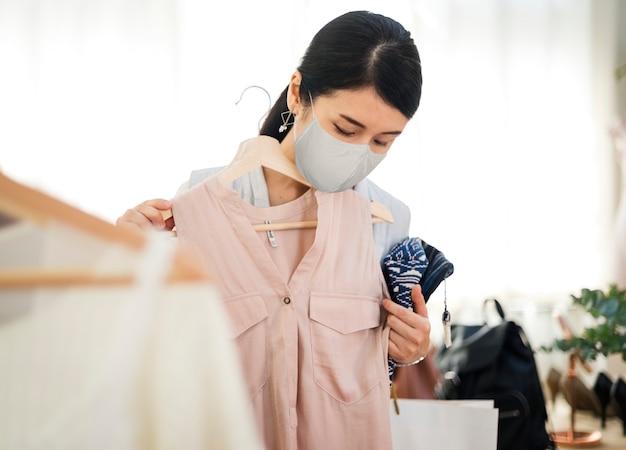 Distanciamiento social covid-19, cliente con máscara comprando ropa