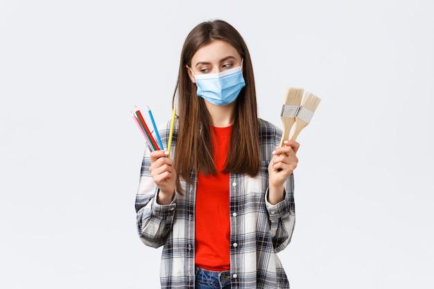 Distanciamiento social, ocio y pasatiempos en el brote de covid-19, concepto de coronavirus. niña sonriente complacida en máscara médica comienza a dibujar, mira lápices de colores, muestra pinceles de pintura.