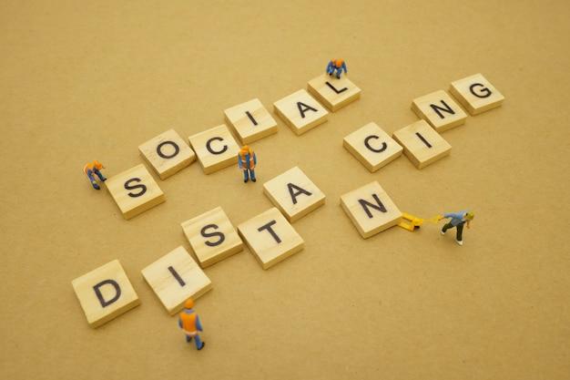 Distanciamiento social. las personas en miniatura se mantienen separadas para reducir la infección por el virus covid 19. mantener la distancia social