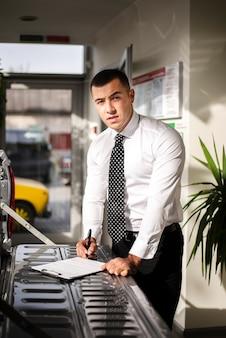 Distribuidor de automóviles guapo firmando documentos