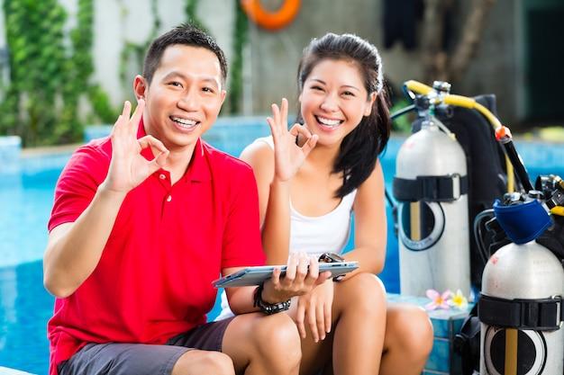 Dive master y estudiante en escuela de buceo asiática