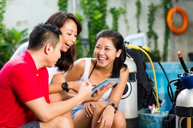 Dive master y estudiantes en escuela de buceo asiática