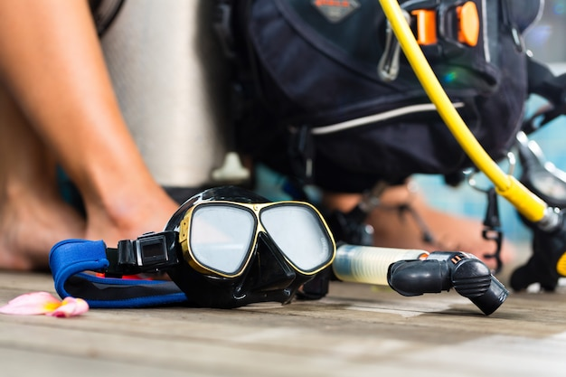 Divemaster y estudiantes en el curso de buceo en vacaciones usando un traje de neopreno o buceando en primer plano es un tanque de oxígeno