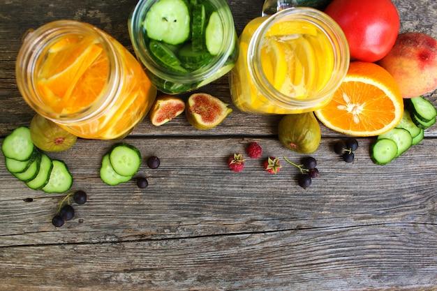 Diversas bebidas, frutas y verduras sobre fondo de madera. vista superior. lay flat.