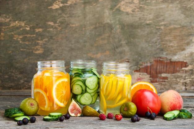 Diversas bebidas, frutas y verduras sobre fondo de madera.