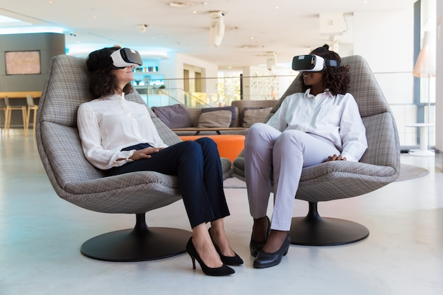 Diversas colegas femeninas con gafas de realidad virtual que hablan entre sí