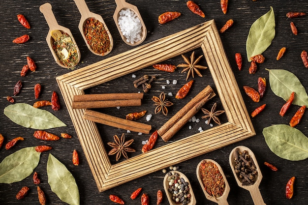 Diversas especias en cucharas de madera en la mesa de piedra oscura.