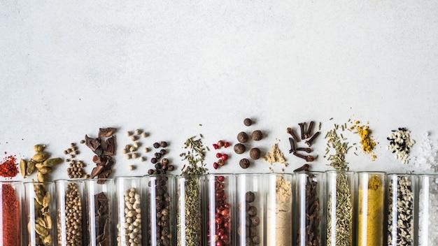 Diversas especias secas en tubos de vidrio sobre fondo gris.
