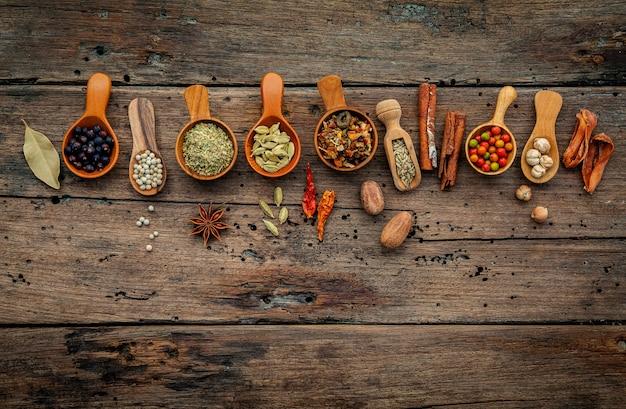 Diversas hierbas y especias en cucharas de madera en fondo de madera.