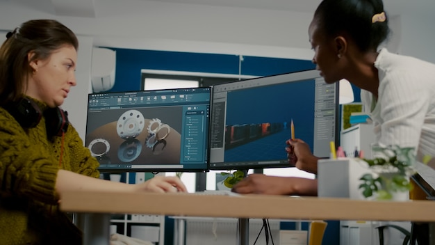 Diversas mujeres desarrolladores de software de juegos que crean una interfaz de juegos sentados en una agencia creativa de inicio co ...