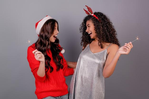 Diversas mujeres felices con brillantes bengalas con sombrero de navidad aislado en gris