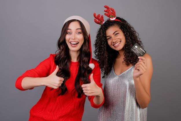 Diversas mujeres felices con tarjeta de crédito de plantilla con sombrero de santa aislado sobre gris