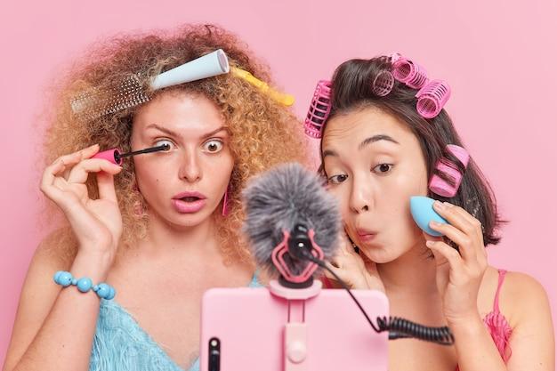 Diversas mujeres jóvenes enfocadas en la cámara web del teléfono inteligente se aplican rímel y la base da maquillaje tutorail para que los suscriptores tengan su propio blog de belleza presente cosméticos de belleza aislados sobre fondo rosa.
