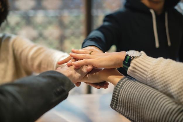 Diversas personas apilando las manos juntas