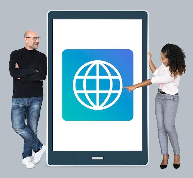 Diversas personas de pie junto a una tableta con el icono de www