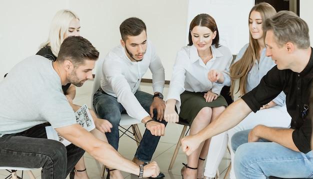 Diversas personas sentadas en círculo extienden las manos en la práctica del equipo de la sesión de terapia de grupo
