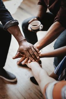 Diversas personas uniendo sus manos en el medio.