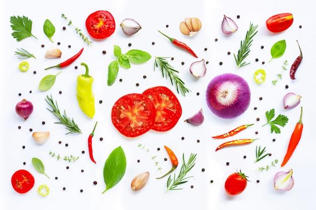 Diversas verduras frescas y hierbas encendido sobre el fondo blanco.