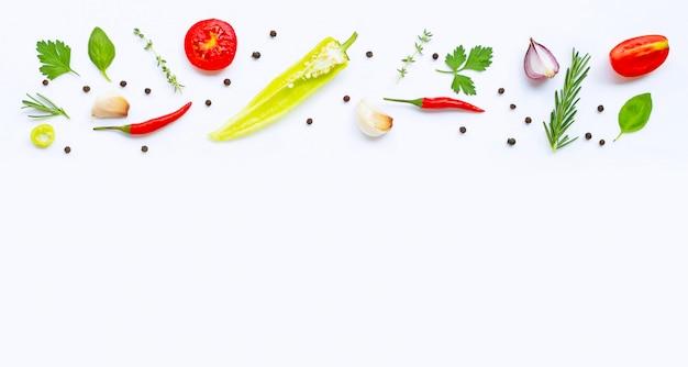 Diversas verduras y hierbas frescas en el fondo blanco con el copyspace. concepto de alimentación saludable