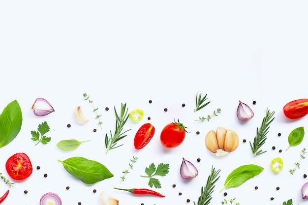 Diversas verduras y hierbas frescas sobre fondo blanco.
