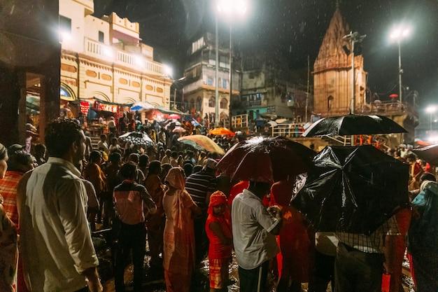 Diversidad abarrotada de personas esperando bendecir bajo la lluvia