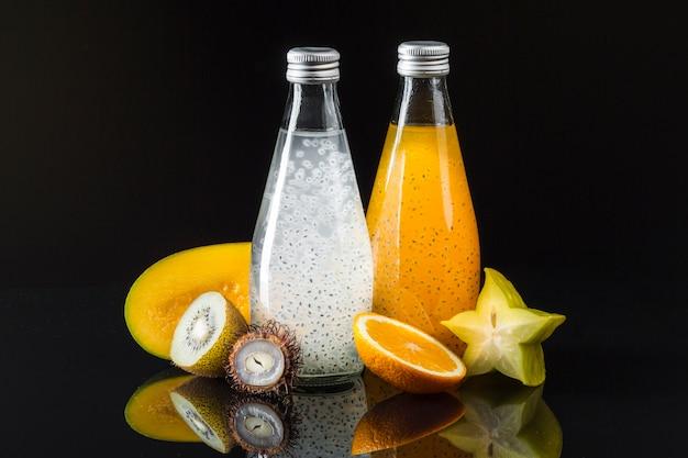 Diversidad de jugos con frutas sobre fondo negro.