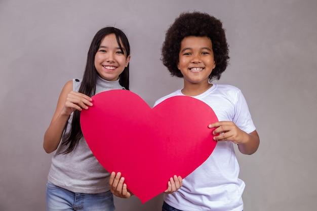 Diversidad. niño japonés y negro sosteniendo una tarjeta en forma de corazón sobre fondo gris con espacio para texto. día del niño