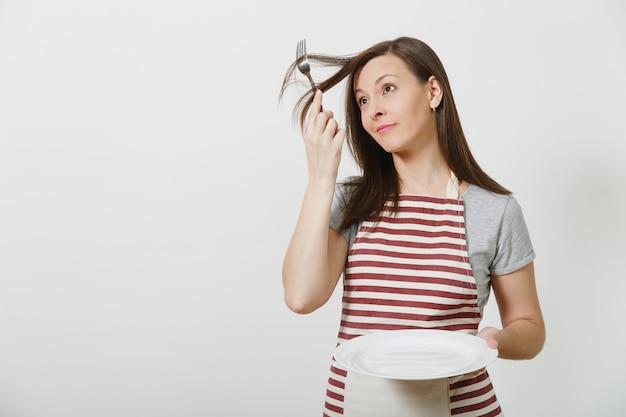 Diversión joven ama de casa morena loca en delantal de rayas camiseta gris aislado ama de llaves mujer sosteniendo blanco plato vacío tenedor en el pelo como peine cepillo