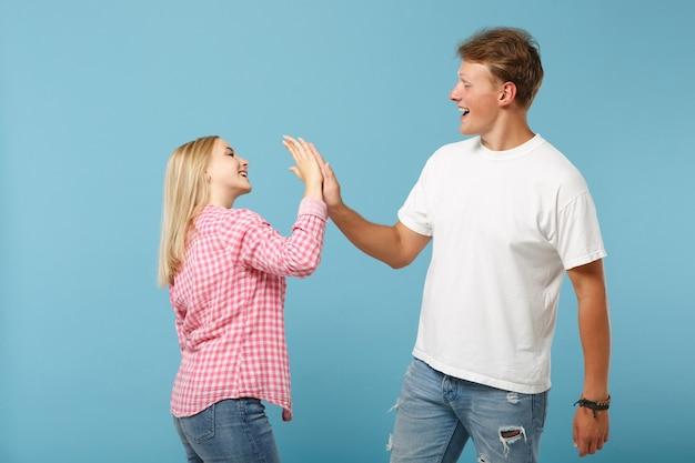 Diversión joven pareja amigos chico chica en blanco rosa diseño en blanco vacío camisetas posando