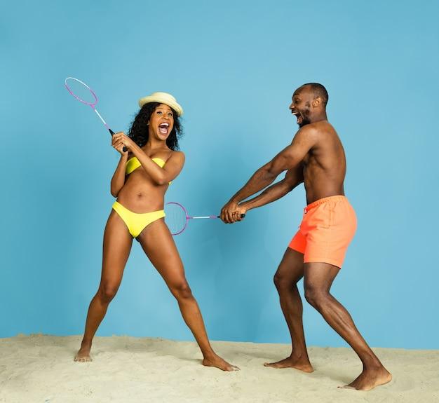 Diversión más loca. feliz pareja joven afroamericana jugando bádminton sobre fondo azul de estudio. concepto de emociones humanas, expresión facial, vacaciones de verano o fin de semana. frío, verano, mar, océano.