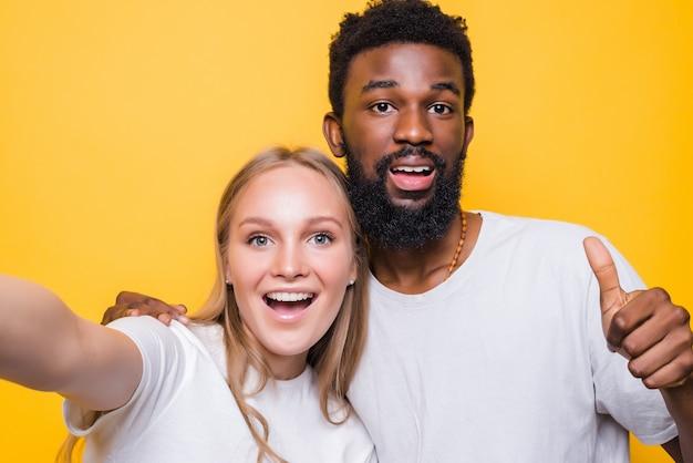 Diversión selfie. pareja interracional alegre tomando autorretrato juntos, mirando a cámara y sonriendo, posando sobre pared amarilla