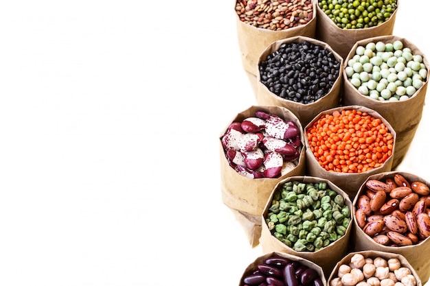 Diverso conjunto de surtido de legumbres indias en bolsas de papel saco aislado sobre fondo blanco.