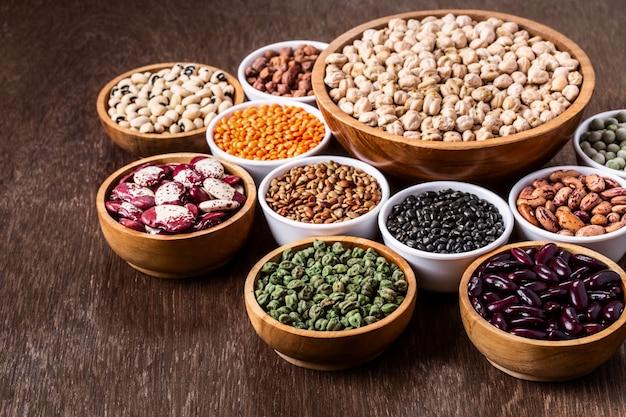 Diverso sistema del surtido de legumbres indias en cuencos en fondo de madera con el copyspace.