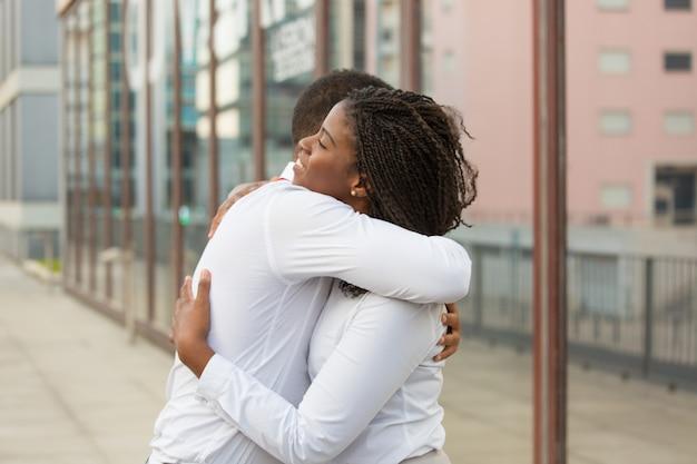 Diversos amigos cercanos abrazándose afuera
