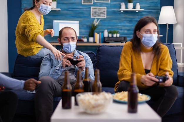 Diversos amigos que intentan ganar jugando videojuegos con un joystick se divierten usando una mascarilla para evitar la propagación del coronavirus en el momento del brote global. concurso de juegos, cerveza y palomitas de maíz.