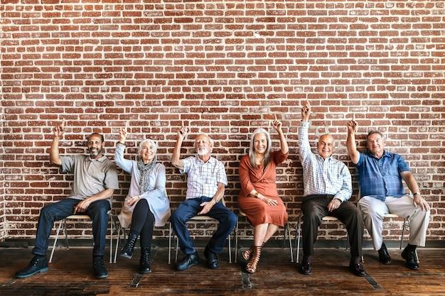 Diversos ancianos apuntando con el dedo índice hacia arriba