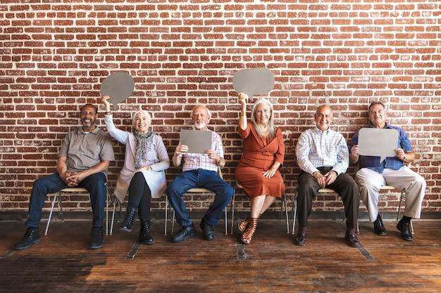 Diversos ancianos mostrando tableros en blanco