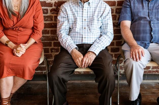 Diversos ancianos sentados en una fila contra un fondo de pared de ladrillo