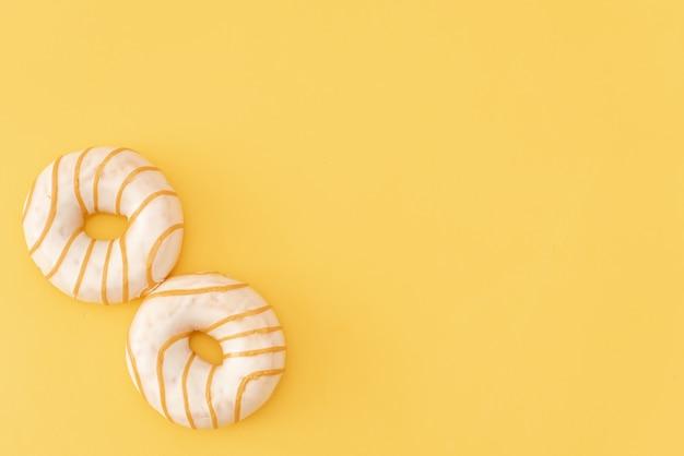 Diversos buñuelos adornados en el movimiento que cae en fondo rosado. dulces y coloridos donuts cayendo o volando en movimiento.