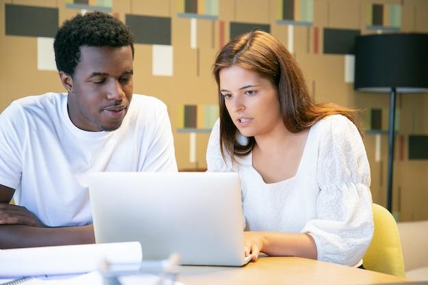 Diversos diseñadores enfocados viendo juntos la presentación del proyecto en una computadora portátil, sentados a la mesa y hablando, discutiendo el proyecto de diseño