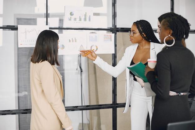 Diversos empleados escuchando a la gerente femenina. mujer hablando en una reunión de grupo. afroamericano.