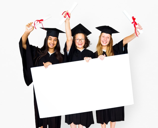 Diversos estudiantes con toga y birrete que muestran un retrato en blanco de un espacio de copia