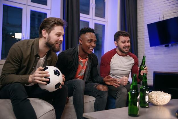 Diversos fanáticos del fútbol que animan a su equipo favorito y beben cerveza en casa, copian espacio