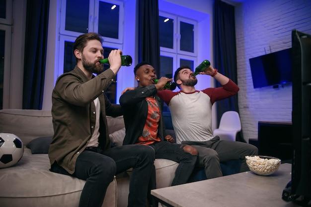 Diversos fanáticos del fútbol que animan a su equipo favorito y beben cerveza en casa, copie el espacio