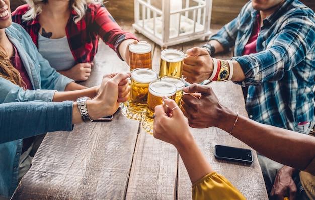 Diversos jóvenes felices celebrando juntos brindando cervezas