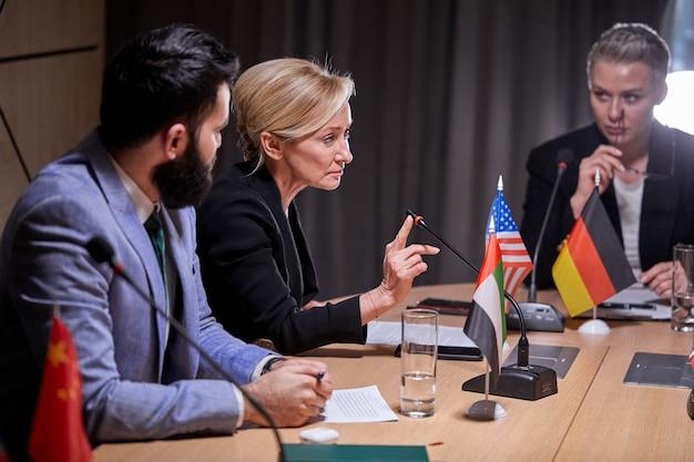 Diversos líderes políticos sentados y escuchando a una mujer mayor hablando por el micrófono en una conferencia de prensa en la sala de juntas, reunidos para discutir ideas
