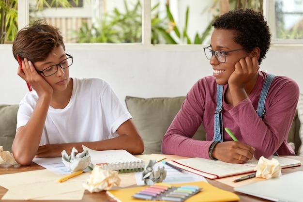 Diversos niños y niñas se encuentran para hacer la tarea.