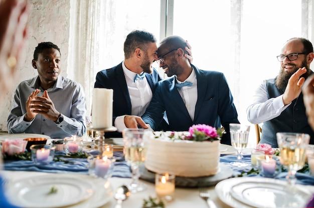 Diversos recién casados pareja gay en la mesa de recepción