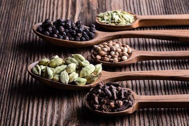 Diversos tipos de especias indias enteras en primer de madera de las cucharas.