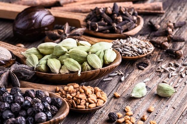 Diversos tipos de especias indias enteras en primer de madera del fondo.
